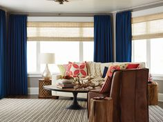 Photo of Budget Blinds - Santa Rosa, CA, United States. Go contemporary with woven wood shades featuring blue pinch pleat curtains and vibrant print pillows.