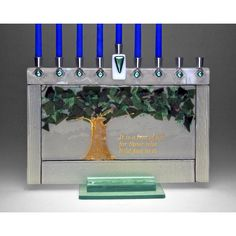"Sara and Michael Beames creates this Tree of Life Menorah. The Tree of Life is depicted in glass confetti and frit, surrounded by textured glass with dichroic accents. In gold type are the words ""It i"
