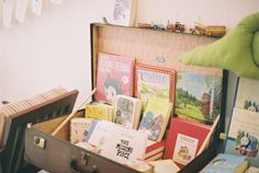 Children's books displayed in suitcase. This would be an excellent way to display the 'Travel the World' books.