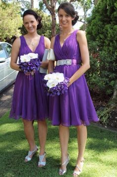 Orchid purple short bridesmaid dresses. Cocktail length. Silver shoes. Side bun hairstyle. Purple and white colour palate. Orchid flower bouquets.