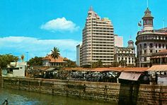 SINGAPORE WATERFRONT SKYLINE WITH ASIA INSURANCE BUILDING, OCEAN BUILDING (RIGHT) AND HAWKER STALLS AT COLLYER QUAY - 1960