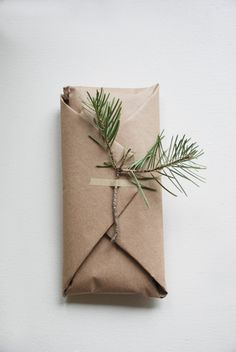 Wrapping presents and gifts with brown paper and giving accents to it with fresh flowers or leaves.