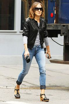 Sarah Jessica Parker gave photographers a smile as she walked her son to school early on May 29th. Before the day heated up, SJP kept warm in cuffed jeans, leather bomber jacket, and accessorized with Ray Bans shade, a crossbody purse, and platform clogs!