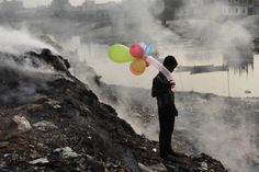 A boy plays with balloons by Buriganga river as smoke billows from a dump yard in Dhaka, Bangladesh. By Andrew Biraj
