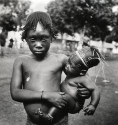 Africa | A young Mangbetu girl carrying a baby. ca. 1949 | ©Marcolin