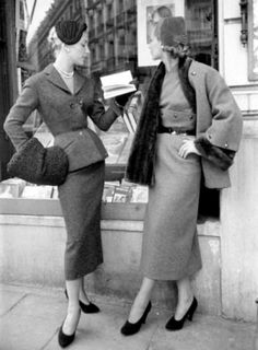 Two models reading while standing outside a bookshop wearing tweed suits from French designer Pierre Balmain's autumn/winter collection. Picture Post, Paris Picks Up Her Skirts, August 29, 1953. Credit: Kurt Hutton. Model on left wears a red suit with a black astrakhan hat and muff. Model on right wears a brown skirt and a nutria-lined coat.