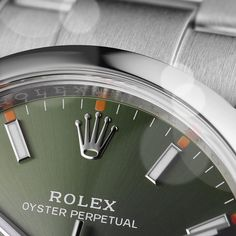 The olive green dial with orange hour marker accents of a 34 mm Oyster Perpetual. #Rolex #OysterPerpetual #ThroughTheLoupe