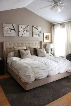 Neutral master bedroom with beige upholstered headboard with white linen bedding. I love bedrooms with vaulted ceilings, they just feel more romantic. Natural oak hardwood floors with perfect area rug placement. Triptych placed over the headboard finishes off the look. Perfect way to style your master bedroom.