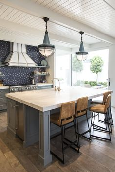 """In kitchens, cooks need a lot of light. Well-lit countertops are ideal, but it's important to include lighting for decorative purposes, too,"" says Amato. ""A colored drop fixture over an island is the perfect way to make a statement."""