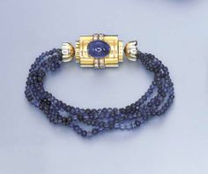 A SAPPHIRE BEAD AND DIAMOND BRACELET  Of five sapphire bead strands, joined by a sculpted and polished clasp, of rectangular form, centering upon a cabochon sapphire, vertically flanked on either side by twin circular-cut diamond lines, 19.5 cm.