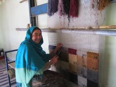 Zainab, an ARZU weaver, smiles while working in our two-story Loom Room in our Women's Community Center