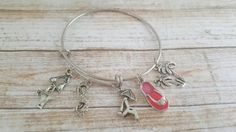 This fun, tropical beach bracelet features a stainless steel, sturdy metal bangle with silver plated charms.  Charms include palm trees, a bikini, and pair of sunglasses, a lounge chair and an enamel pink flip flop.    The bangle does not open but is expandable.      Personalize this bracelet by adding a crystal birthstone and/or initial charm to the bracelet.  https://www.etsy.com/listing/498238250/add-a-birthstone-add-an-initial-add-on?ref=shop_home_active_4      This fashionable bangle…