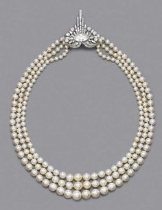 A 1925 RARE ART DECO PEARL AND DIAMOND NECKLACE   Comprising three rows of graduated pearls measuring 9.8 to 4.2 mm. diameter to the baguette and circular-cut diamond clasp with graduated baguette-cut diamond tassles and oval-shaped centre.