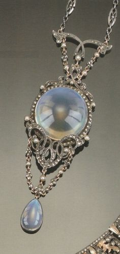 AN ARTS AND CRAFTS MOONSTONE, MARCASITE AND HALF-PEARL PENDANT. Centred on a circular cabochon moonstone with silver scroll mounts and garland chains to a drop-cut moonstone drop, on a chain, apparently unmarked. Source: Christie's 20th Century Jewellery, 12 October, 2000. #ArtsAndCrafts