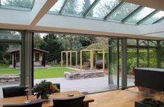 Een serre met glazen vouwwanden. De pui kan in z'n geheel geopend worden. Het glazen dak zorgt voor veel licht in de woning en een buitengevoel.