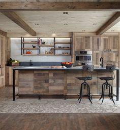 Cette splendide cuisine de chef, fabriquée dans un esprit de valorisation optimale de l'espace de travail, harmonise parfaitement le chic et l'aspect rustique. L'utilisation du chêne, au cachet vintage, en panneaux plats de style Shaker permet d'accentuer l'effet « bois de grange » désiré par les propriétaires. La présence de poignées et de structures en métal noir, conçues de manière artisanale, rehausse avec raffinement l'esprit ancestral de cette cuisine...