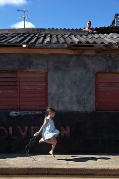 Yadria Aliana Cala plays in front of her house while a man repairs the roof, 2011 Narrative Photography, Color Photography, Light Photography, Street Photography, Advanced Photography, Robert Frank, People Around The World, Travel Around The World, Cuba