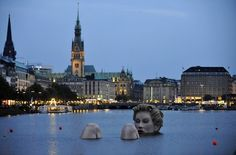 """A 'mermaid' sculpture created by Oliver Voss is seen in the late evening hours on Alster lake in Hamburg August 3, 2011. The four-metre-high sculpture dubbed """"Riesen-Nixe"""" (grand mermaid) or """"Badenixe"""" (bathing beauty) will be on display until August 12. REUTERS/Morris Mac Matzen (GERMANY - Tags: SOCIETY)"""