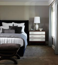 Solid bedding in crisp white with a coverlet and accent pillows in varied bedroom ideas    shades of textured gray cover navy blue upholstered bed frame dotted with nailhead trim.