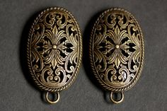 A set of two (2) bronze brooches created from from gently rounded shield-like disks with delicate fretwork and bails for hanging cascade necklace