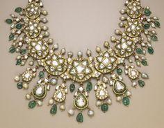 An Indian enamel, diamond and gold necklace designed as a series of graduated floral clusters of table-cut diamonds, surmounted by a line of cultured pearls, suspending a fringe of cultured pearls, emeralds, and table-cut diamond and emerald pear-shaped clusters; the reverse of red and green enamel floral motifs on a white background; length: 17in