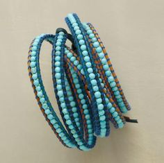 """Chan Luu lines up nearly 250 turquoise beads bordered with variegated leather, wrapped with complementary threads. Wraps five times, fastening with a sterling button-and-loop. 32""""L."""