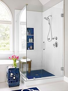 For a walk-in shower with classic style, incorporate a blue and white color scheme. Navy blue hues repeat on this shower's floor tile and shelving backsplash. #walkinshower #walkinshowerideas #bathroommakeover #showerideas #bhg Small Bathroom With Shower, Small Showers, Narrow Bathroom, Simple Bathroom, Walk In Bathroom Showers, Corner Showers, Bathroom Modern, Master Bathrooms, Dream Bathrooms