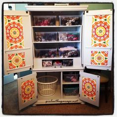 Turn a TV armoire into clothes storage by adding shelves and baskets.  Love that fabric on the doors!  #organization