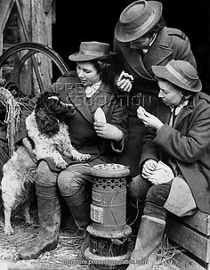 Land Girls with a Spaniel dog during a lunch break on a farm in Sevenoaks, Kent (1942).