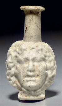 A ROMAN GLASS DOUBLE HEAD FLASK   CIRCA LATE 1ST-2ND CENTURY A.D.   Opaque white in color, mold-blown, each side with a head of Medusa, with wild flowing snakey locks, the snake tails knotted below her chin, her lips parted, with a protruding chin and bulging eyes, the vessel with a tapering cylindrical neck, the flaring mouth with the rim folded out and then in