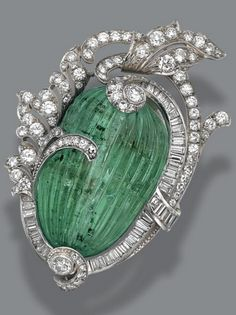 Brooches An Art Deco carved emerald and diamond pendant-brooch, circa The melon-shaped carved and fluted emerald within a foliate frame set with numerous round, single-cut and baguette diamonds weighing approximately carats, mounted in platinum. Bijoux Art Deco, Art Deco Jewelry, Bling Jewelry, Jewelry Box, Jewelry Design, Geek Jewelry, Jewlery, Jewelry Necklaces, Art Nouveau