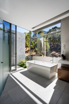 Minimalist Bathroom // white oversized soaking tub in this modern bathroom // A Family Home With 270° views In Cape Town by SOATA and Janie Lazard Interiors