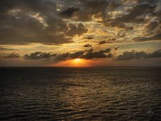 The sun casts orange rays down on the Atlantic Ocean off the coast of Belize just before sunset.