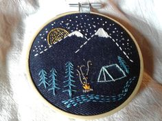 Embroidery hoop art. Tent camping, mountains, campfire. Stitched on denim.