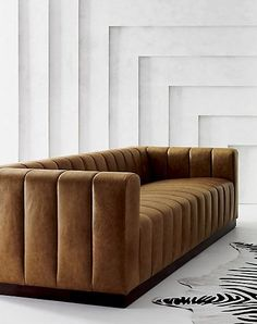 real grandeur. Cushy channels of rich saddle-colored top-grain leather line the length of this generous sofa by Mermelada Estudio. Soft to the touch with a sit on the firmer side, this unexpectedly deep sofa is comfy enough to really stretch out. Low profile wood base with dark walnut stain brings added warmth to this vintage Italian modern statement piece. Learn about Mermelada Estudio on our blog. CB2 exclusive.