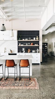 Black and white kitchen with open shelving, vertical subway tile