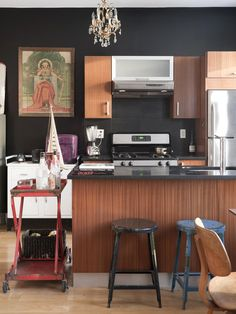 eclectic kitchen design by Bob and Courtney Novogratz.  Love the vintage metal stools, eames molded plywood chair, rolling cart, and chandelier.