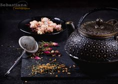 Variety of dry tea with teapot - Tranditional eastern metal teapot with the variety of tea, infused with herbs and flowers over the black stone slate board