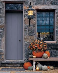 "create a pumpking ""pot"" by carving it out and planting mums inside. I love the gold sprayed pumpkins. The stone work on this house is gorgeous too!"