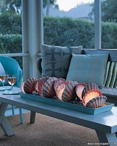 Nice idea. Place large shells on a tray with pebbles or sand and insert a tea light inside each arrangement. Hollow sea urchins would look great too.