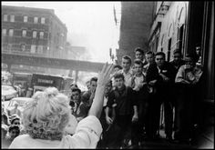Bob Henriques USA. New York City. US actress Marilyn MONROE waves to a crowd of teenage boys. 1958.