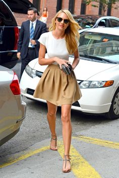 Candice Swanepoel tight white top, tan pleated skirt, sandals and sunglasses