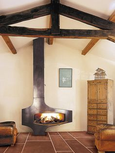 Modern fireplace juxtaposed with exposed beams and large tile floor. Yum.