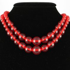Bakelite Beads - Red - Cherry Prystal - Vintage.  This necklace is made of two strings of graduated cherry juice Prystal Bakelite beads. The lower string measures 16 inches long (without the clasp). The inner string measures 15 inches. The necklace beads pass the Semichrome test. The clasp does not. These beads are clear and in excellent vintage condition.