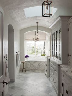 beach front bathroom features a barrel ceiling fitted with a skylight over an arched nook filled with a marble clad tub under window illuminates by a French candle chandelier.