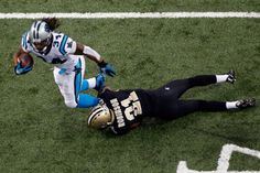 NEW ORLEANS, LA - DECEMBER 30: James Dockery #31 of the Carolina Panthers is tackled by Patrick Robinson #21 of the New Orleans Saints at the Mercedes-Benz Superdome on December 30, 2012 in New Orleans, Louisiana. (Photo by Chris Graythen/Getty Images)