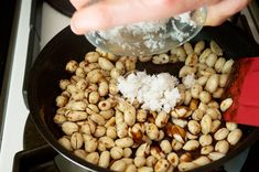 Adding the grated coconut flakes to the melted coconut sugar and toasted peanuts for Kashata (Tanzanian Coconut Peanut Brittle)