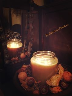 A rather large candle sitting on top of my antique armoire with a reflection of my bed by ye olde Crow primitives