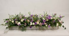 Top table trough flower arrangement. Purple, lilac and white wedding theme.