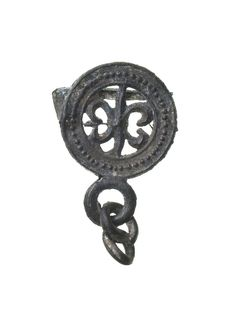 Pilgrim badge Part of a pilgrim badge of the Virgin Mary, probably from Canterbury, Kent. This badge is in the form of a fleur-de-lys (one of the symbols of the Virgin) within a circular frame which would have been linked to a medallion or pendant which is now missing. Other similar badges depicting Thomas Becket are known from Canterbury so it is likely that these circular framed badges that linked to pendants were made in Canterbury too.  Production Date: Late Medieval; 15th century